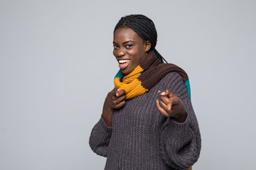 Young african woman pointed on you wearing sweater and scarf isolated on grey wall. Winter concept