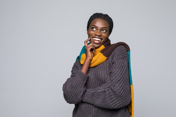 Young african woman in sweater and scarf isolated on grey wall. Winter concept