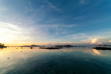 Dramatic sky seascape with rock in sunrise scenery and beautiful reflection in the sea