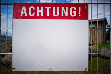 """Schild mit der Aufschrift """"Achtung"""" an einem Zaun"""
