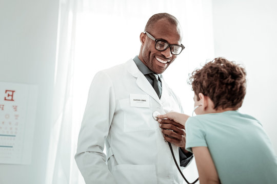 Cheerful international male person working in clinic