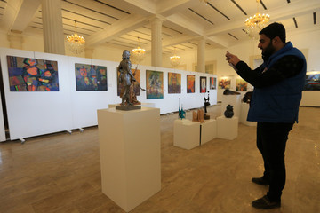 A visitor takes a picture of a statue during an art exhibition at the Mosul Museum Hall in Mosul
