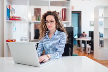 Portrait of pretty young business woman in glasses sitting on workplace, using laptop.