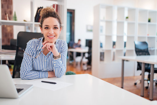Portrait of a beautiful smiling female office worker sitting at workplace.