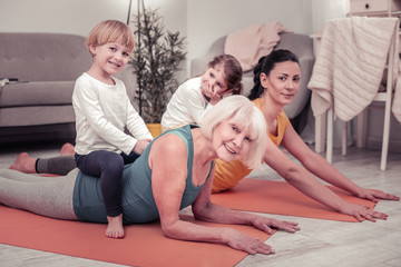 Women involving children in doing stretching exercises