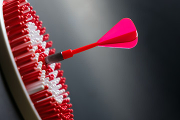 Red dart arrow hitting the center of dartboard for goal achievement conceptual
