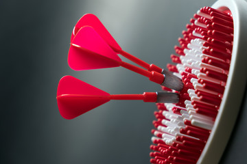 Three red dart arrows hitting the center of dartboard for goal achievement conceptual