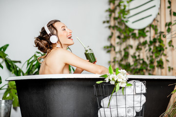 Young relaxed woman listening to the music and drinking smoothie while lying in the retro bathtub at the beautiful bathroom with green plants