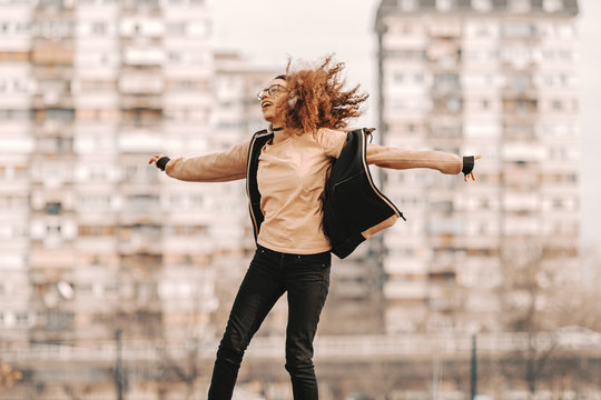 Beautiful mixed race hipster teenage girl with curly hair enjoying music and jumping. In background blurred buildings.