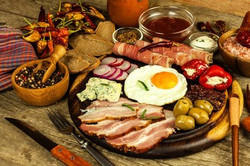 Fried egg on a wooden board. A hearty breakfast with ham and vegetables. Eggs and ham.