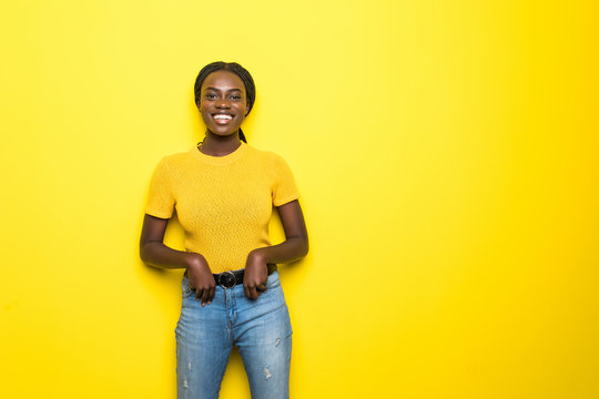 Beauty portrait of young african american girl posing on yellow background, looking at camera, smiling. Studio shot.