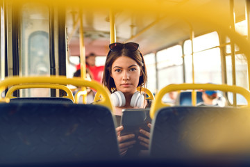 Young girl sitting in bus and holding tablet.