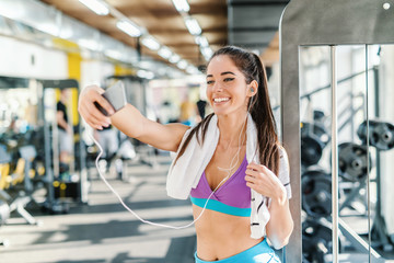 Caucasian woman with towel around neck and earphones in ears smiling and taking selfie while standing in a gym.