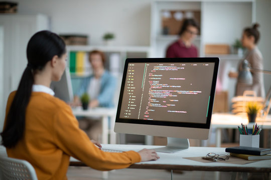 Young female programmer in casualwear sitting by desk in front of computer screen and analyzing coded data