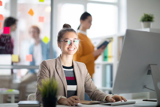 Happy casual businesswoman looking at you while sitting by desk in front of computer screen in working environment