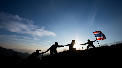 Leader handing Thailand Flag and climbers help A Team to conquer the summit in teamwork in a fantastic mountain landscape at sunset. Helping hand concept and international day of peace and teamwork.