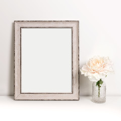 Picture frame standing on table with flower in decorative bottle, mock-up