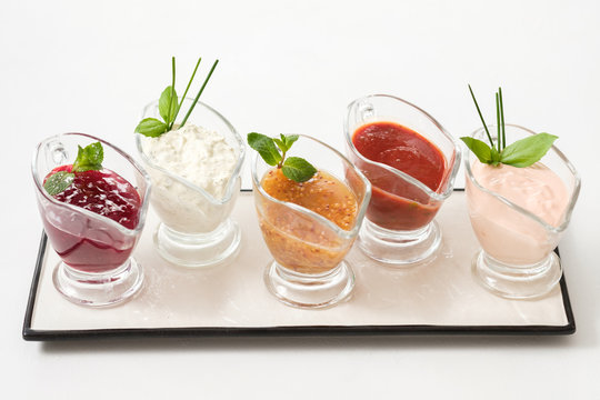 Gourmet cooking concept. Set of assorted sauces. Glass gravy boats on white ceramic platter.