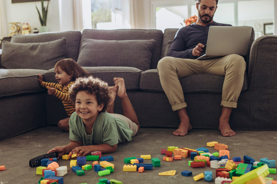 Man babysitting his kids and working from home