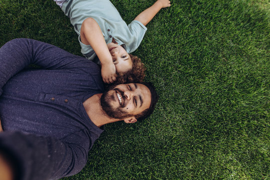Father and son relaxing in a park lying on ground