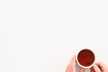 Hands holding cup of tea. Coziness concept. Copy space on white background.
