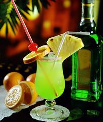 Una copa con un cóctel de piña, naranja y un licor.