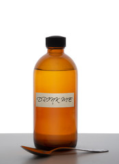 Brown glass medicine bottle with spoon and label saying 'Drink me'. Magic potion, panacea, pharceutical concept. Isolated against white background.