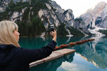 Travel and adventure. Travel hiker makes photo of beautiful landscape on smartphone, Dolomites Mountaines. Braies Lake (Lago di Braies), hiking on alpine lake, Alps, Dolomites, Italy, Europe
