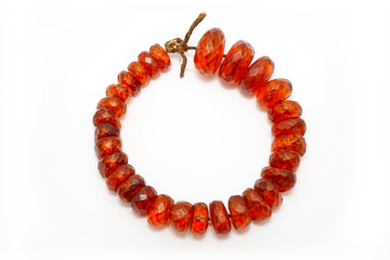 Very beautiful amber beads on a white background. Large orange red amber beads with flat edges. Jewelry women. Sun Stone. Advertising for jewelry shop. Natural mineral. Ancient resin. Sunstone