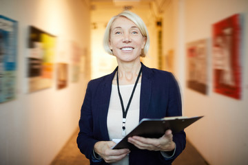 Waist up portrait of mature female manager holding clipboard posing in art gallery looking at camera, copy space