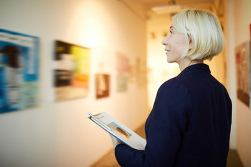 Side view portrait of mature female manager holding clipboard working in art gallery, copy space