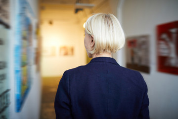 Back view portrait of unrecognizable woman looking at pictures in art gallery, copy space
