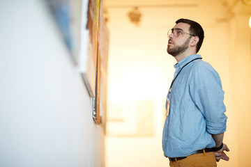 Side view portrait of bearded man looking at pictures in art gallery, copy space