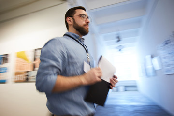 Low angle portrait of museum worker holding clipboard passing art gallery hall, copy space
