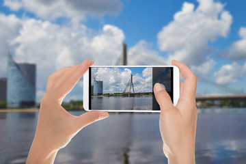 A man is making a photo of cable-stayed bridge in Riga in summer sunny day on a mobile phone