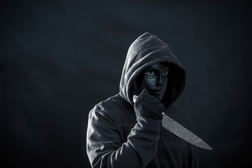 Hooded man with black mask holding knife in the dark