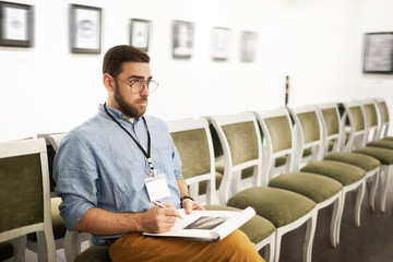 Portrait of bearded young man taking notes while looking at pictures in art gallery or museum, copy space