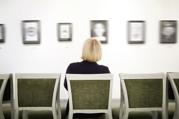 Back view portrait of elegant woman sitting on velvet chair looking at pictures in art gallery or museum, copy space