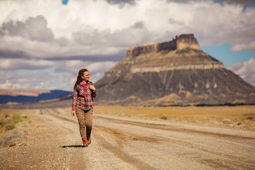 hitchhiker woman walking on a road in USA