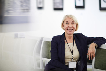 Portrait of smiling mature woman wearing blank name tag sitting on chair in art gallery or museum, copy space
