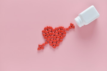 A heart was embroidery by arrow shape of medicine pills pouring out of white bottle on pink background. Concept of Valentine's Day or pharmacy, Medical.