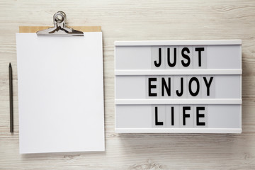 Lightbox with text 'Just enjoy life', clipboard with sheet of paper and pencil on a white wooden surface, top view.