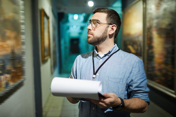 Waist up portrait of bearded man holding clipboard while looking at pictures in art gallery or museum, copy space