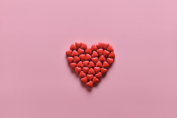 A heart shape of medicine pills on pink background. Concept of Valentine's Day or pharmacy, Medical.