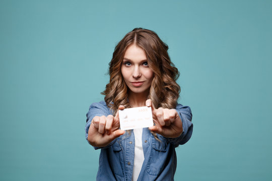 Smiling young woman holding credit card. isolated portrait.