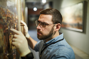 Close up  of bearded museum worker inspecting painting for restoration, copy space
