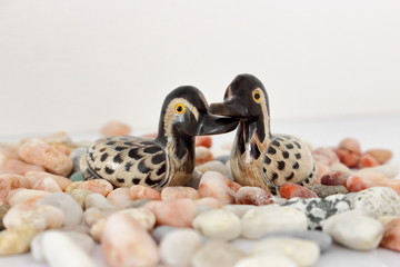 Valentine's day concept. Couple in love, just married or honeymoon concept. Couple of stone mandarin ducks toy with coral and gray pebbles.