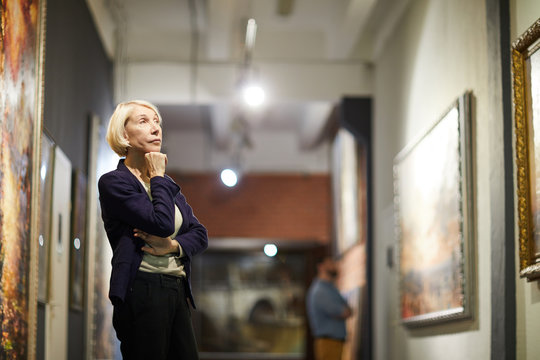 Portrait of pensive mature woman looking at paintings standing in art gallery or museum, copy space