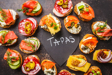 Assorted spanish tapas with fish, sausage, cheese and vegetables. Dark background, top view.