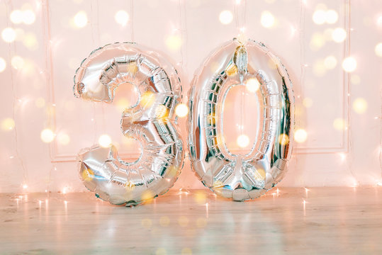 Silver foil birthday balloons number 30 with glitter lights.